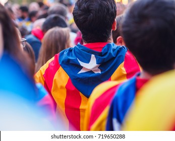 Young man carrying the Catalan independence flag on his shoulders during a demonstration in Barcelona