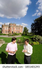 Young man carrying a cup of tea in his hand smiling at his friend who is holding a mobile phone while walking in a garden in front of a huge manor on sunny day