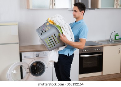 Young man carrying heavy laundry basket by washing machine at home