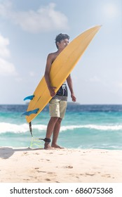 a young man carrying his surfboard at beach
