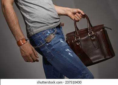Young man carrying a leather bag against grey background