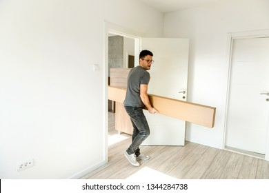 Young man carrying new furniture