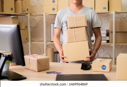 Young man carrying a pile of cardboard boxes in his office. Business owner checking and packing online order to delivery during sale seasonal.Online Shopping and e-Commerce ,SME concept.