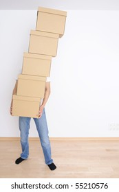 Young man carrying a stack of boxes