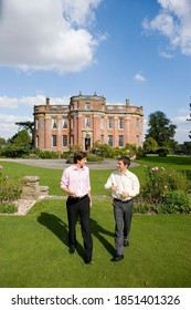 Young man carrying a tea cup in his hand smiling at his friend while walking in a garden in front of a huge manor on sunny day