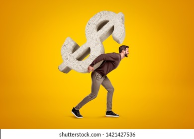 Young man in casual clothes carrying big stone dollar sign on his back on yellow background. People and objects. Money and finance. Digital art.