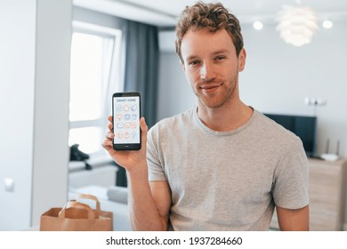 Young man in casual clothes is indoors controlling smart home technology.