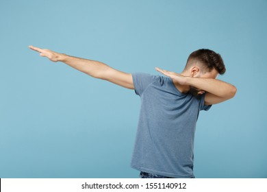 Young man in casual clothes posing isolated on blue wall background, studio portrait. People sincere emotions lifestyle concept. Mock up copy space. Showing dab dance gesture