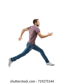 Young man in casual clothes running on white background