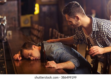 Young man in casual clothes is sleeping near the bottle of beer on a bar counter in pub, another man is waking him up