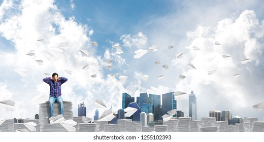 Young man in casual clothing sitting among flying paper planes with cloudly skyscape on background. Mixed media.