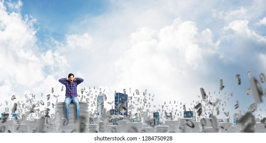 Young man in casual clothing sitting among flying letters with cloudly skyscape on background. Mixed media.