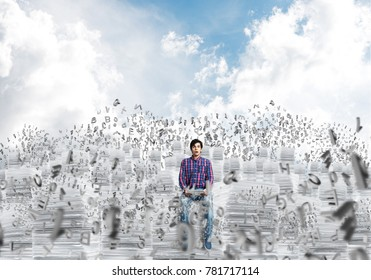 Young man in casual clothing sitting on pile of documents among flying letters with cloudly skyscape on background. Mixed media.