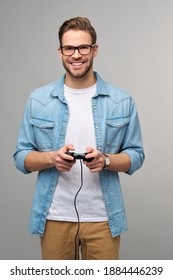 young man in casual jeans shirt holding joystick or gamepad playing game