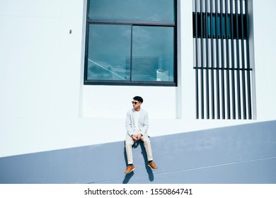 Young man in casual look sitting at the slope of a building in a summer.