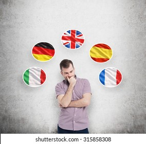 Young man in casual shirt holds his chin and thinks about which language to study. Italian, German, United Kingdom, Spanish and French flags in the bubbles are flying above the person.