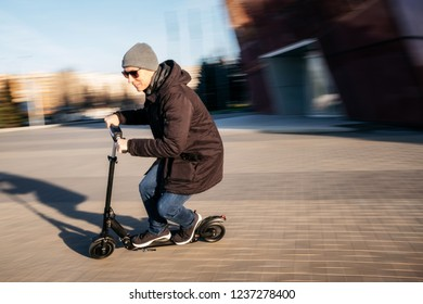 Young man in casual wear on electric kick scooter on city street in motion blur in autumn