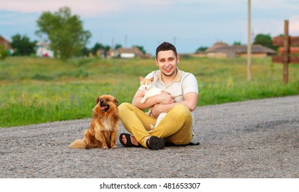 a young man with a cat and a dog are sitting on the road, the guy in the yellow jeans holding a cat in her arms, a dog sitting on asphalt