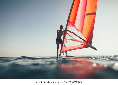 Young man catch the wind for surf. Low angle view of windsurfer sailing on windsurf board