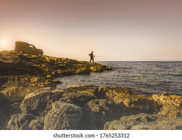 A young man catches fish in the sea in the morning.Silhouette of a fisherman on the background of sky, sea and horizon.