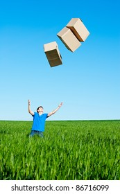 young man catching boxes on green field against blue sky