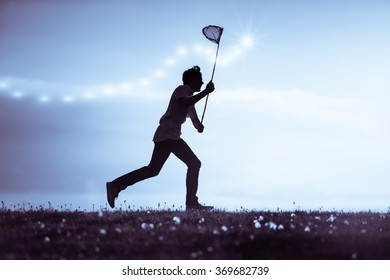 Young man catching insects at dusk running along the skyline silhouetted against a cloudy blue sky brandishing his net