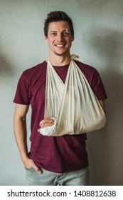 Junge Mann in Kausalkleidung mit Gips auf seinem Arm oder Handgelenk mit Heften und Pflaster über seinem Auge.  Verletzten Mann, der einen guten und glücklichen Geist aufrecht erhält, lächelt.