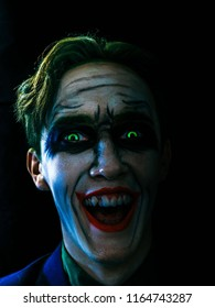 Young man celebrates halloween. Dark creepy white face, green eyes and hairs, laughing in the dark. Halloween in October.