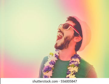 Young man celebrating carnaval holiday. Wearing sunglasses, hat and flower necklace. Color filter and copy space.