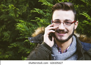 young man with cellphone in the forest