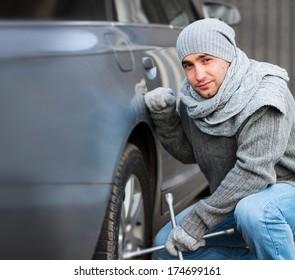 Young man changing a car wheel
