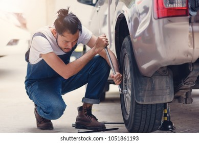 Young man changing flat tire on the road .Replacing the tires on the car. Flat tire. Attaching a spare wheel. Lifting the car on the jack. Accident with punctured tires.