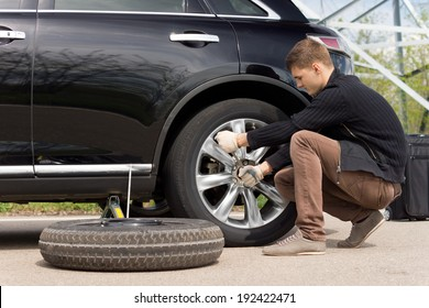 Young man changing the punctured tyre on his car loosening the nuts with a wheel spanner before jacking up the vehicle