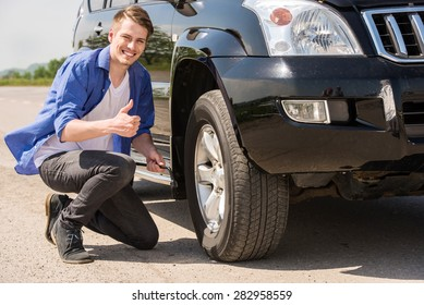 Young man changing the punctured tyre on his car.