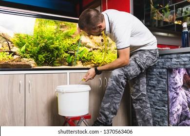 Young man changing water in aquarium using siphon.