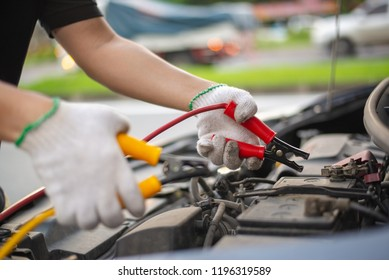 Young man charging battery car with electricity trough jumper cables on the country road, insurance and service concept.