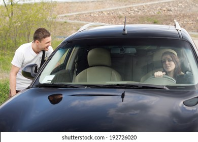 Young man chatting up a female driver talking to her through the passenger window as he tries to persuade her to give him a lift