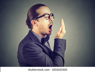 Young man checking his breath with hand test gesture.