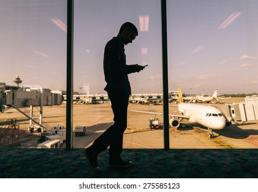 Young man checking his phone while waiting his flight in the airport - Business man at airport and airplane and airport in the background