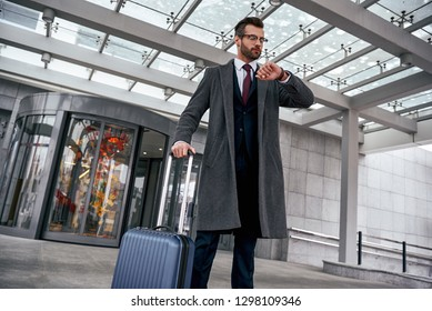 Young man checking his watch and pulling suitcase