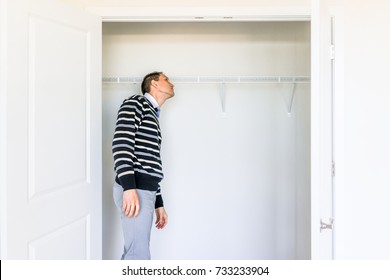 Young man checking looking inside small closet in new room after or before moving in, during open house