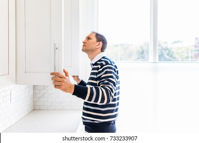 Young man checking looking inside empty kitchen modern cabinets by window after or before moving in
