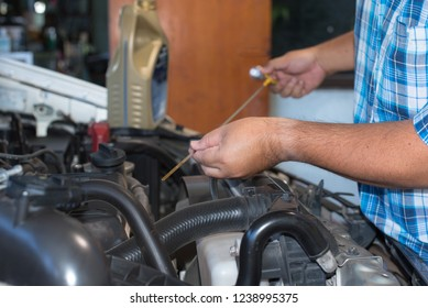 Young man checking the oil level in car engine.