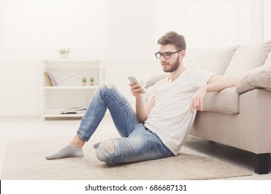 Young man checking social media on smartphone at home sitting on the floor. Stylish boy in casual in glasses, copy space
