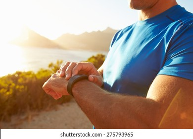 Young man checking time on his sports watch
