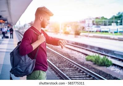 Junger Mann, der die Uhr am Bahnhofsbahnsteig überprüft - Schüler-Pendler bei Bahnabfahrten im pensiven Gesichtsausdruck - Alltägliches Lifestyle-Konzept mit Sonnenhalo-Filter