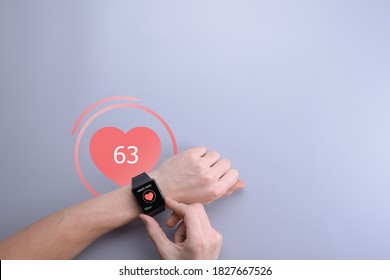 A young man checks and monitors his heart rate through an app in a smart watch. Smartwatch on hand, top view.