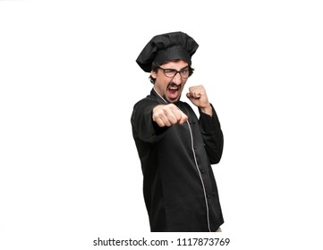 young man chef with an angry, aggressive and menacing pose, ready for the fight, showing fists furiously and belligerently.