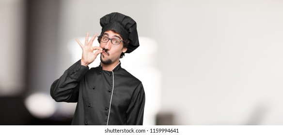 "young man chef gesturing ""zip it"" with hand, demanding silence or secrecy with a serious, stern look."