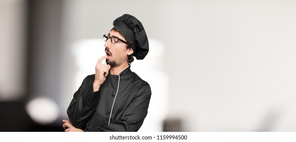 young man chef with a goofy, dumb, silly look, feeling shocked and confused at a recent realization, not really understanding an idea.